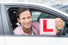 Learner driver smiling and holding l plate Royalty Free Stock Images