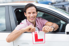 Learner driver smiling and tearing l plate Stock Image