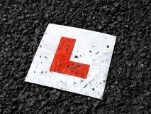 Learner drivers plate against black tarmac. Accident concept image royalty free stock photos