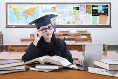 Learner with graduation gown studying in class Stock Photo