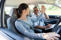 Learner instructor high five. Cheerful young learner driver and driving instructor high five royalty free stock photo