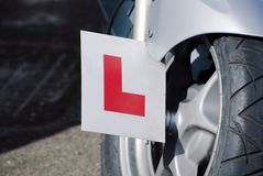 Learner L Plate on Motorbike. Closeup of an L-plate attached to a silver motorbike.  Front wheel and mudguard of motorbike visible.  Standing on concrete Stock Photos