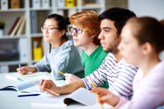 Learners at lecture. Row of students sitting at lecture in college Stock Image