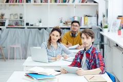 Learners at lesson. Students with gadgets listening to teacher at lesson Royalty Free Stock Photo
