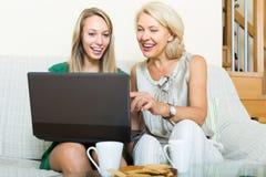 Learnig de la mujer para utilizar el ordenador portátil de la muchacha Fotos de archivo libres de regalías