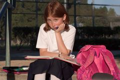 Learning. Schoolgirl in uniform is sitting with open book and pencil. She is learning. the book is on her lap. Her pencil case is taken out of bag and open. The Royalty Free Stock Photography