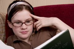Learning. Attractive teen studying on the couch royalty free stock photography