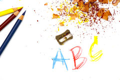 Learning. Bright colorful image of freshly sharpened colored pencils, red, blue and yellow, with shavings on white drawing paper with numbers, letters and pencil Stock Photos