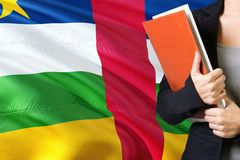 Learning African language concept. Young woman standing with the Central African Republic flag in the background. Teacher holding. Books, orange blank book stock photo