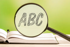Learning the alphabet abc. With a book and a magnifying glass Royalty Free Stock Image