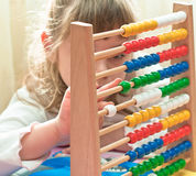 Learning arithmetic. Little Girl contemplates the basics of arithmetic on his abacus Stock Images
