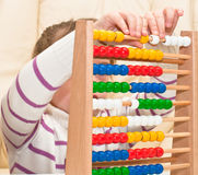 Learning arithmetic. Little Girl contemplates the basics of arithmetic on his abacus Royalty Free Stock Images