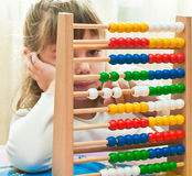 Learning arithmetic. Little Girl contemplates the basics of arithmetic on his abacus Stock Photography