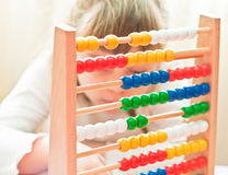 Learning arithmetic. Little Girl contemplates the basics of arithmetic on his abacus Royalty Free Stock Photo