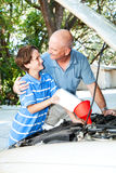 Learning Auto Maintenance. Father teaching his son how to put oil in the family car stock photo