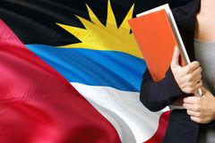 Learning Barbudan language concept. Young woman standing with the Antigua and Barbuda flag in the background. Teacher holding. Books, orange blank book cover royalty free stock photo