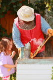 Learning from the bees. Little girl learning apiculture from her great-grandfather Stock Photography