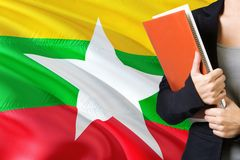 Learning Burmese language concept. Young woman standing with the Myanmar flag in the background. Teacher holding books, orange. Blank book cover royalty free stock photo