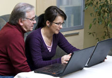Learning Computers. A senior man and a middle-aged woman learning how to use a laptop computer Stock Image