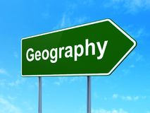 Learning concept: Geography on road sign background. Learning concept: Geography on green road highway sign, clear blue sky background, 3D rendering Royalty Free Stock Images
