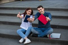 Learning concept. Smiling University students with thumb up gesture outdoors on Campus sitting on stairs with books in hand. Confident students showing books and stock images