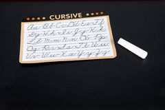 Learning Cursive. Guide to writing cursive english letters on a blackboard with a piece of chalk stock photo