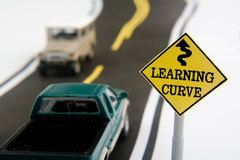 Learning Curve. Toy vehicles on road next to learning curve road sign Royalty Free Stock Photo