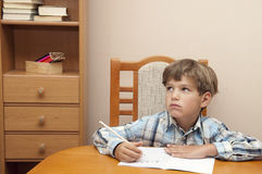 Learning is difficult. Boy with plaid shirt writes in a notebook Royalty Free Stock Photo
