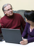 Learning discussions. A woman (daughter) and a senior man (father) talking about serious matters in front of a laptop computer Royalty Free Stock Image