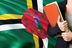 Learning Dominican language concept. Young woman standing with the Dominica flag in the background. Teacher holding books, orange. Blank book cover stock photos