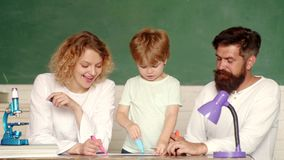 Learning and education concept. Young happy family schooling math together. Cute pupil and his father and mother making. Schooling work. Nice family photo of stock video footage