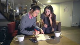 Two young girl preparing for exams drawing the study plan while sitting at the table stock footage