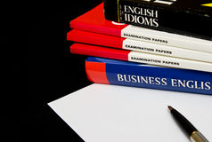 Learning English. Pile of educational books with pen and paper for learning English language, black background Royalty Free Stock Image