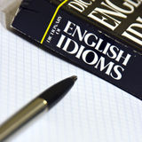 Learning English. English idioms dictionary, a notebook and pen Royalty Free Stock Photo
