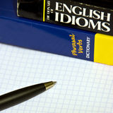 Learning English. English idioms dictionary, phrasal verbs dictionary on a notebook with pen Stock Photo