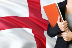 Learning English language concept. Young woman standing with the England flag in the background. Teacher holding books, orange stock image