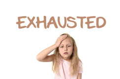 Learning English language vocabulary school card with the word exhausted. And sweet cute little female child touching her head suffering headache looking tired Royalty Free Stock Photo