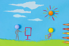 Learning. Figurative teacher teaching figurative pupil on a sunny day on blue sky and green grass background Stock Photography