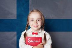Learning finnish language. Smart child girl on the Finnish flag. Background stock photos