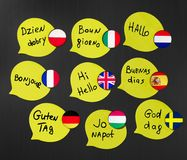 Learning foreign languages ​​courses. Phrase greetings in different languages. Flags of the countries of the studied languages.  stock photo