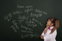 Learning foreign languages. Small girl thinking about foreign phrases stock image