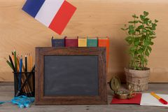 Learning french language concept - blank blackboard, flag of the France, books, pencils, compass. On wooden background Royalty Free Stock Image