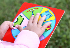 Learning game. Little child playing learning game. Focus on hand and game table Stock Image