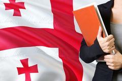Learning Georgian language concept. Young woman standing with the Georgia flag in the background. Teacher holding books, orange. Blank book cover stock image