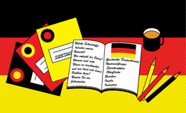 Learning German. Equipment for learning German on the German flag background Royalty Free Stock Photo