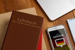 Free Learning German Book And App. Using Phone To Do Exercises Royalty Free Stock Photos - 190903088