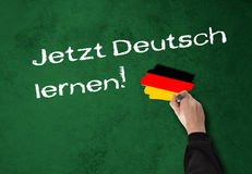 Learning German now!. Man, teacher writes & x22;Learning German now!& x22; on a wall stock photo