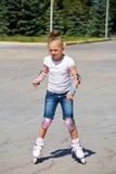 Learning girl on roller skates. In summer stock photography