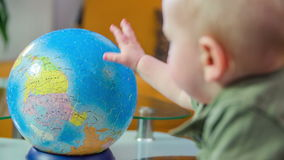 Learning about the globe. Young child standing next to the table and looking at a globe in the living room and he spins it, in slow motion stock footage