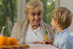 Learning with granny. Happy little boy learning at home with his lovely granny stock image